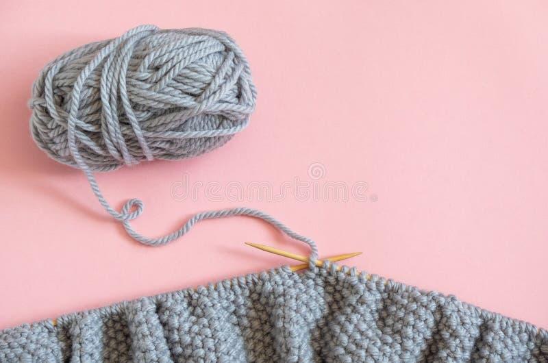 Pezzo di tessuto tricottato grigio sugli aghi con la palla di filato, processo di tricottare sul fondo rosa Copi lo spazio per te immagine stock libera da diritti