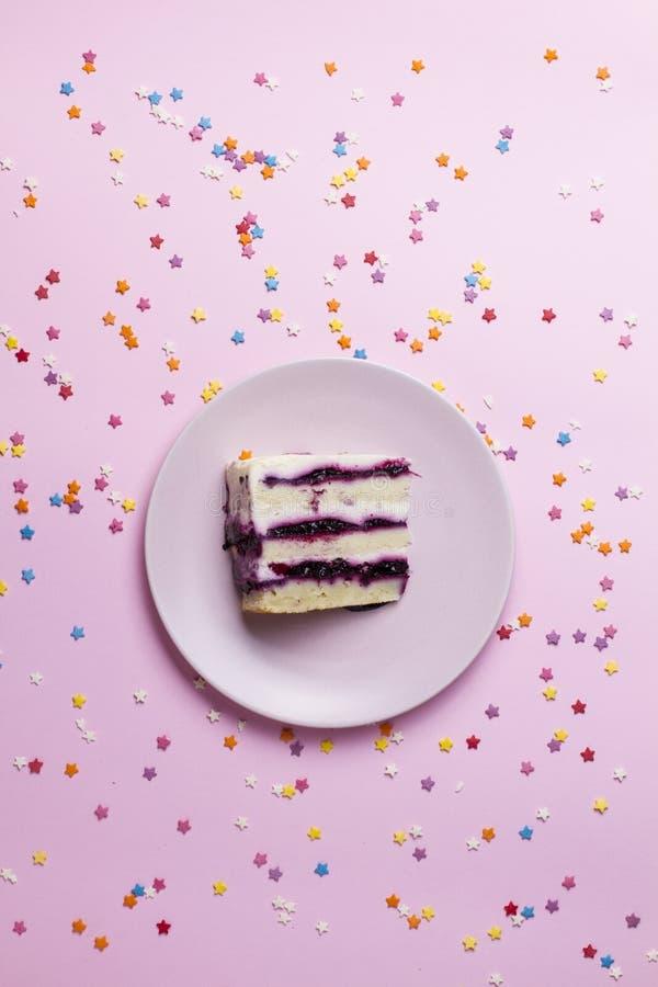 Pezzo di torta di compleanno su un rosa fotografia stock