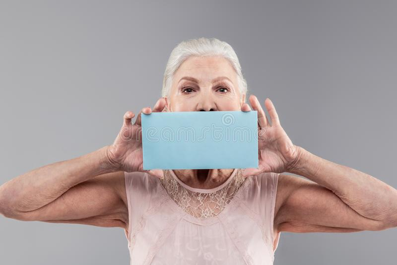 Pezzo di trasporto femminile senior dai capelli corti risoluto di materiale blu-chiaro immagini stock