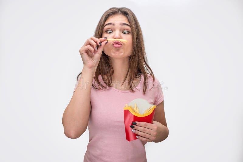 Pezzo divertente e sconosciuto della tenuta della giovane donna di patata fra la bocca ed il naso Lo esamina La carta con altre p fotografia stock