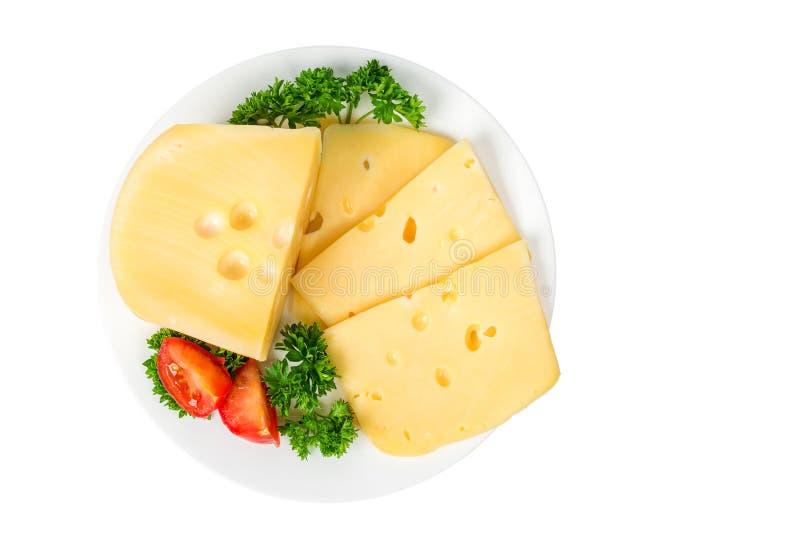 Pezzo e fette di formaggio in un piatto con le erbe ed i pomodori isolati su fondo bianco immagini stock