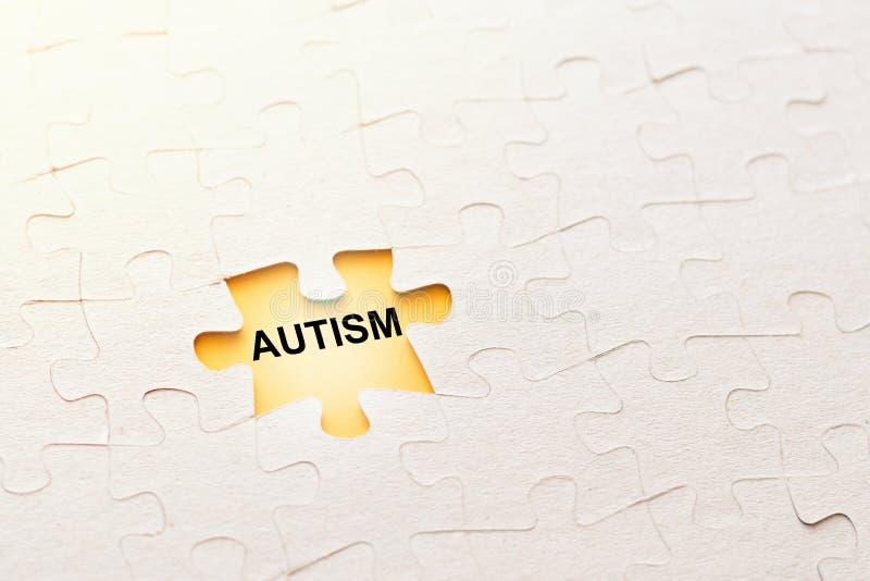 Pezzo mancante di puzzle con autismo su un fondo giallo, concetto dell'iscrizione di problema fotografia stock libera da diritti