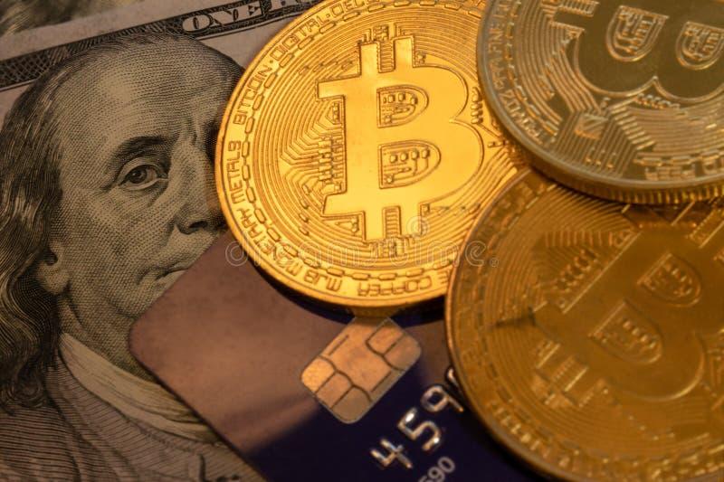 Pezzo-moneta dorata con la carta di credito blu sopra cento dollari di fondo della banconota, cryptocurrency che accetta per il p fotografie stock libere da diritti
