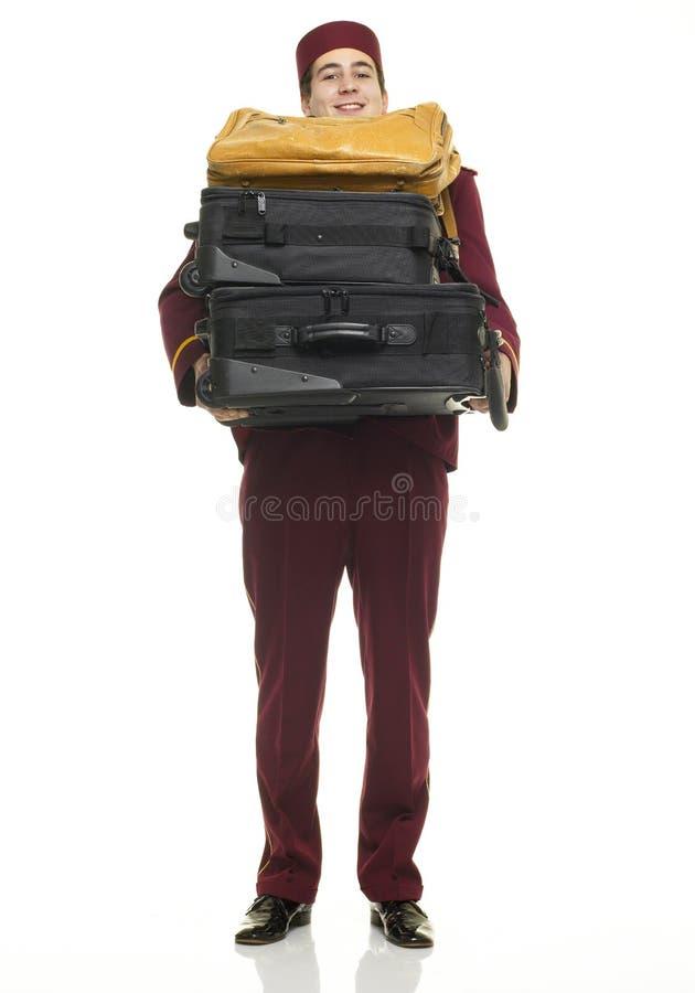 Pförtner trägt Koffer stockbild