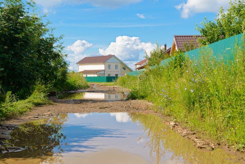 Pfützen auf einem Schotterweg in einem Dorf lizenzfreies stockfoto