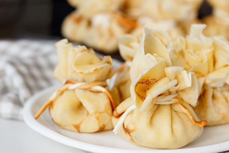 Pfannkuchen angefüllt mit einer Tasche auf einer weißen Platte mit Fleischfüllung lizenzfreie stockfotos