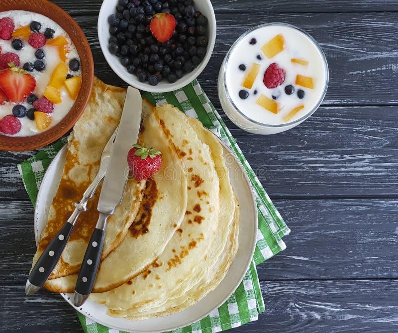 Pfannkuchen, Erdbeeren, Himbeeren, Aprikose, Hüttenkäse, Jogurt auf einem hölzernen Hintergrund stockfotos