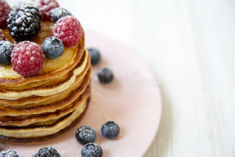 Pfannkuchen mit Beeren auf einer rosa Platte, Seitenansicht Gesunde Sommerfrühstück Nahaufnahme lizenzfreies stockfoto