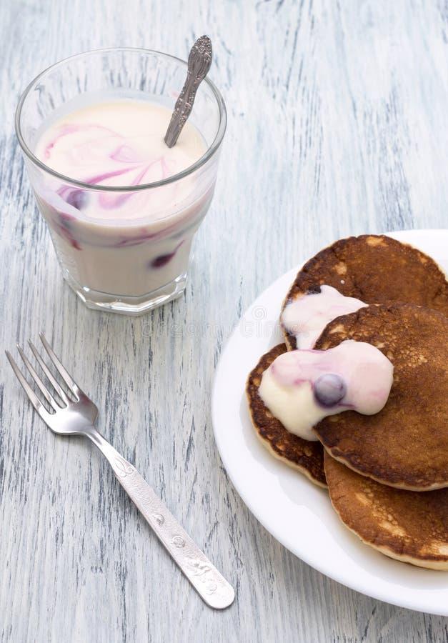 Pfannkuchen mit Beerenjoghurt in einer weißen Schüssel auf einem Holztisch Jogurt mit Korinthen im Glas lizenzfreie stockfotografie