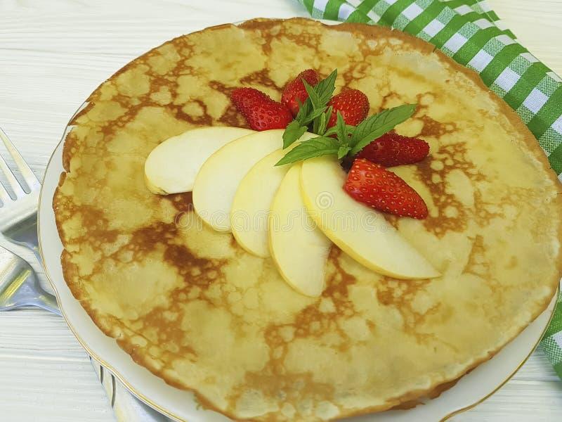 Pfannkuchen mit der Erdbeerapfel-Frühstücksbeere, welche die Nahrung kocht tadelloses Gabeltuch auf weißem hölzernem kocht lizenzfreie stockbilder