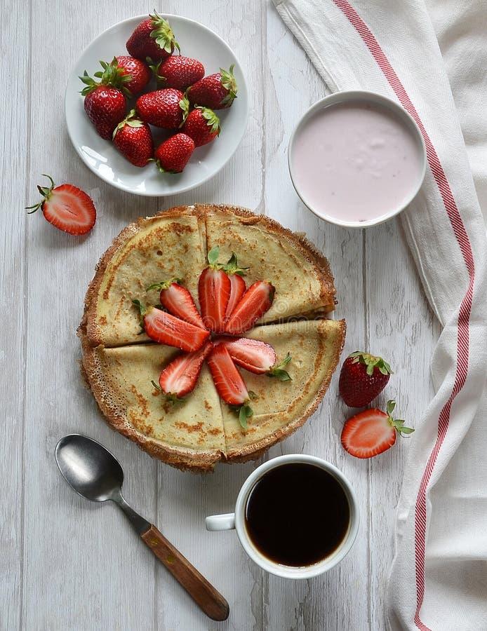 Pfannkuchen mit Erdbeeren, Kaffee und Jogurt auf dem Tisch stockfotografie