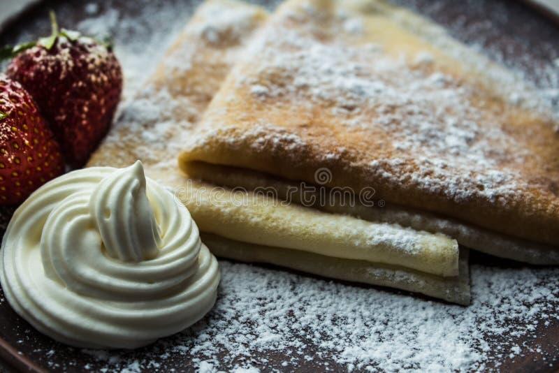 Pfannkuchen mit Erdbeeren Puderzucker und Creme stockbild