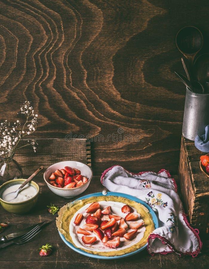 Pfannkuchen mit Erdbeeren und Jogurt auf rustikalem hölzernem Küchentisch, Stillleben stockbild