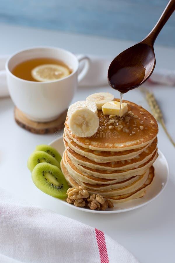 Pfannkuchen mit Früchten, Stau und Kappe des Tees auf einer weißen Tabelle stockfoto