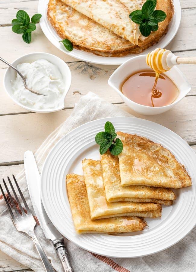 Pfannkuchen mit Honig auf einem h?lzernen Hintergrund lizenzfreies stockfoto