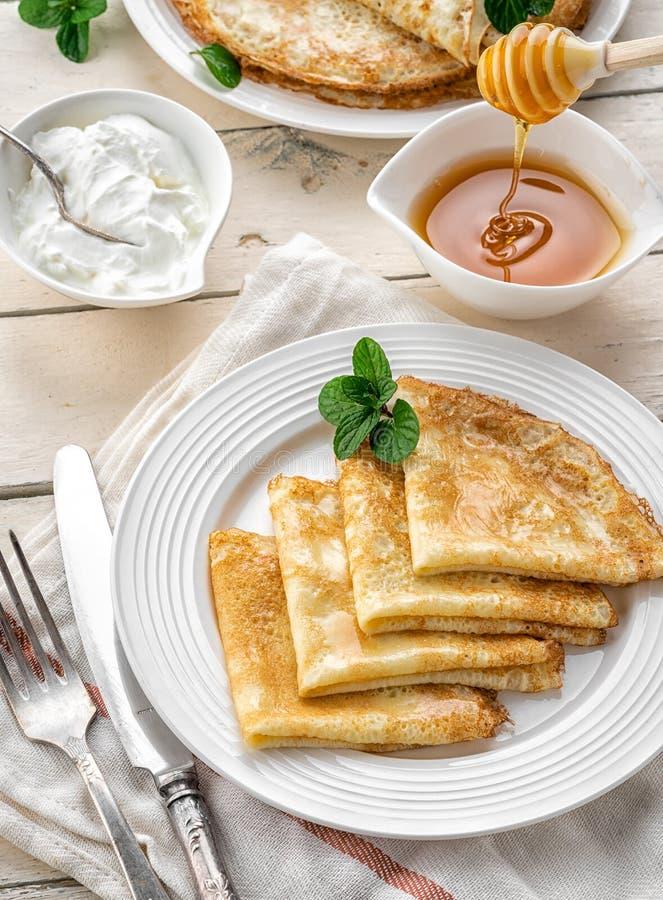 Pfannkuchen mit Honig auf einem h?lzernen Hintergrund lizenzfreie stockbilder