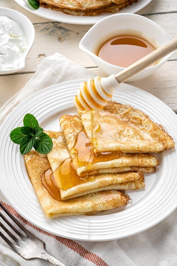 Pfannkuchen mit Honig auf einem h?lzernen Hintergrund stockbilder