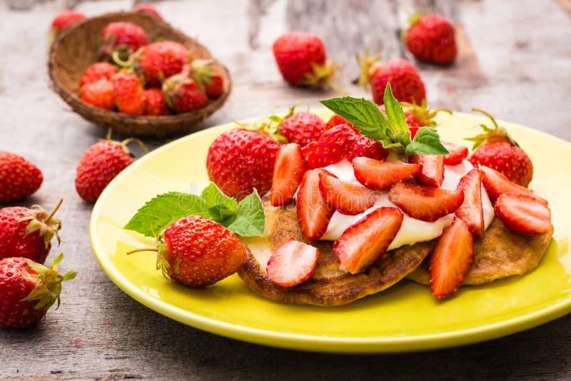 Pfannkuchen mit Jogurt, geschnittenen Erdbeeren und tadellosen Blättern lizenzfreies stockfoto