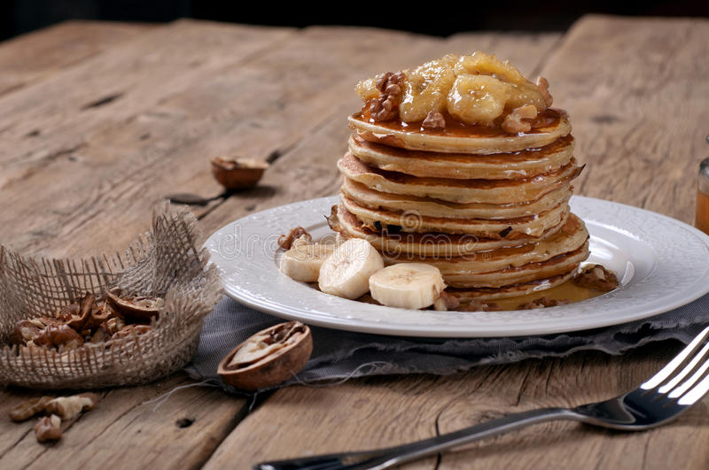 Pfannkuchen mit karamellisierten Bananen, Nüssen und Honig stockfotos