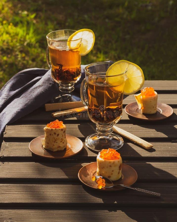 Pfannkuchen mit rotem Kaviar, zwei Gläsern mit Tee und Scheiben von lem stockbild