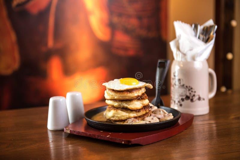 Pfannkuchen mit Wurst und durcheinandergemischten Eiern in einer Bratpfanne stockfotos