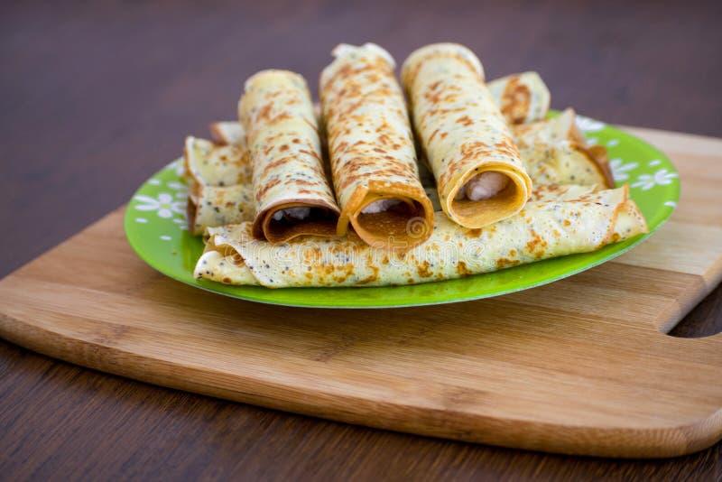 Pfannkuchen rollt mit Hüttenkäse auf einem hölzernen Brett Pfannkuchen mit Käse Shrovetide stockfotografie