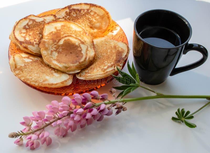 Pfannkuchen und eine Schale der Lupine des schwarzen Kaffees stockfotografie