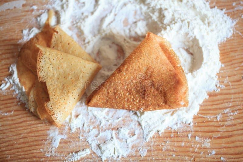Pfannkuchen und Mehl auf dem Tisch stockfotos