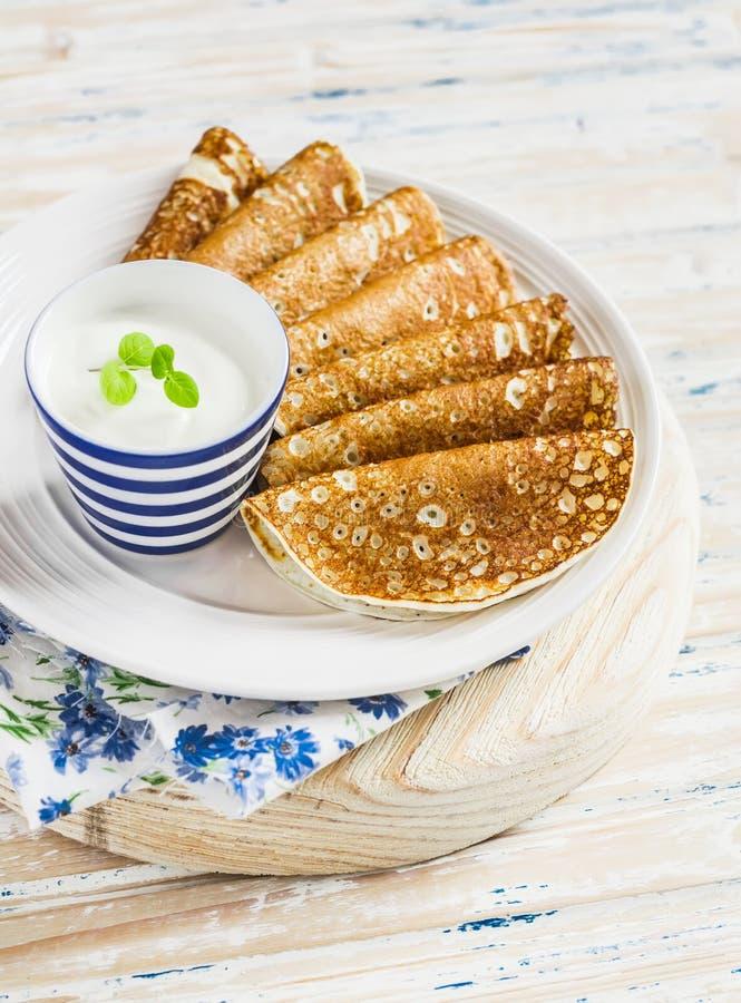 Pfannkuchen und natürlicher Jogurt - köstliches Frühstück auf einem hellen rustikalen hölzernen Hintergrund stockbilder