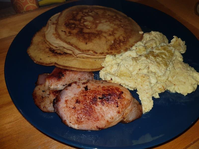 Pfannkuchenfrühstück mit durcheinandergemischten Eiern und Speck stockfotografie