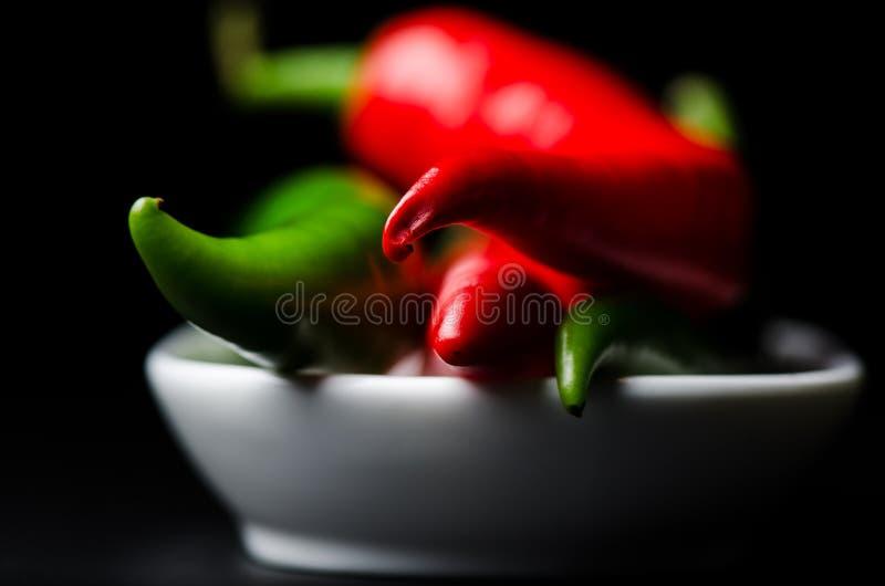 Pfeffer des grünen und roten Paprikas auf schwarzem Hintergrund lizenzfreies stockfoto