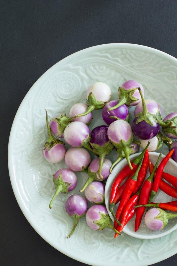 Pfeffer des scharfen Paprikas und purpurrote thailändische Auberginen auf grüne Platten auf einem schwarzen Hintergrund lizenzfreies stockfoto