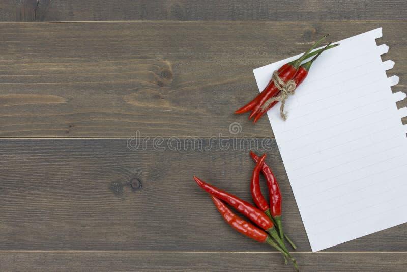 Pfeffer- und Papieranmerkung des roten Paprikas über Holztisch mit Raum des freien Texts stockfotografie