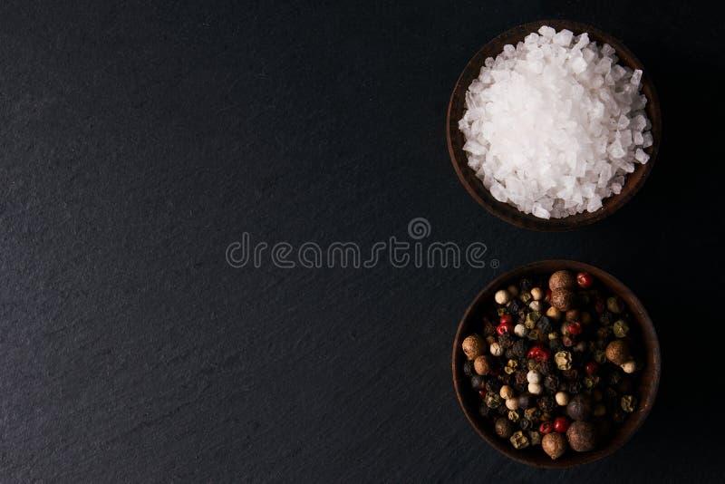 Pfefferkörner und Seesalz in einer hölzernen Schüssel lizenzfreie stockfotos