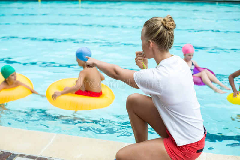 Pfeifender Leibwächter bei der Unterrichtung von Kindern im Swimmingpool stockfotografie