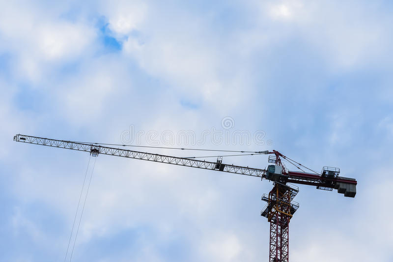 Pfeil des Baukranes für gegen blauen Himmel mit Wolken für das Errichten des neuen sehr hohen Hauses Für Hintergrundgebrauch stockbilder