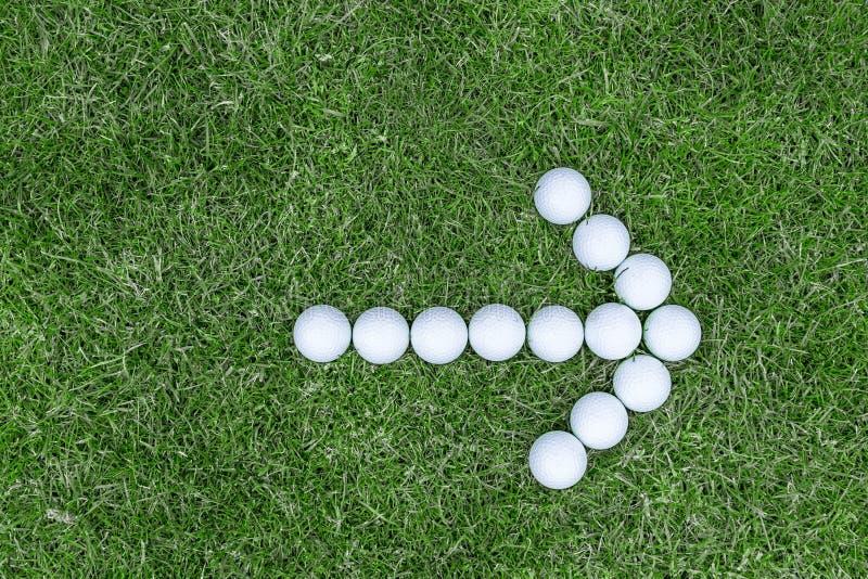 Pfeil von den Golfbällen auf Gras stockfoto