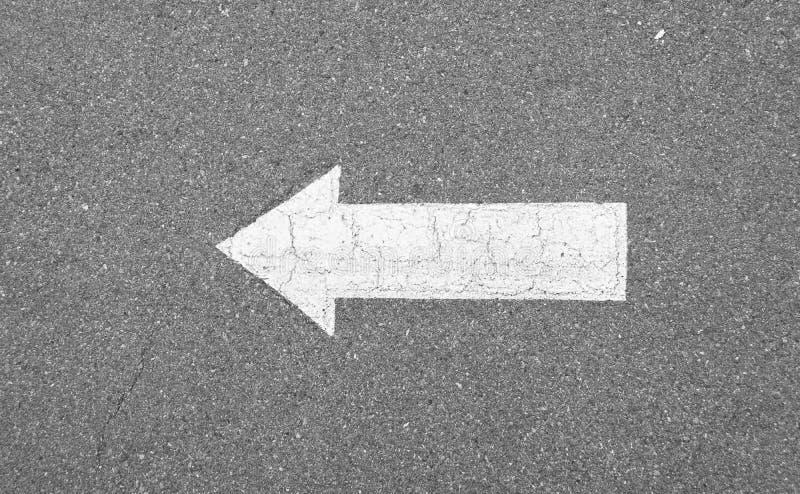 Pfeilzeichen auf konkreter Beschaffenheitsstraße stockfotografie