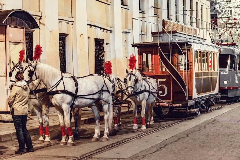 Pferde und Passagierweinlesewagen auf der Stadtstraße im historischen Stadtzentrum vor der Wiederholung von traditionellen Trams stockfotos