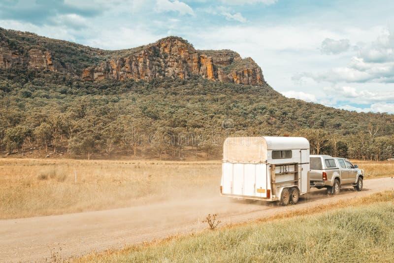 Pferdefloss gezogen durch Vierradantrieb entlang einem Schotterweg in ländlichem Australien lizenzfreies stockbild