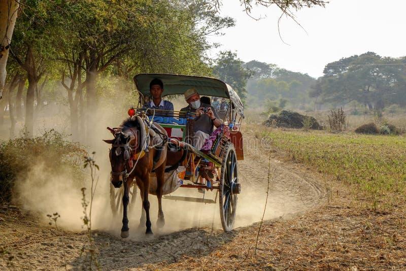 Pferdekutsche auf dem Weg zu Thatbyinnyu-Tempel stockbild