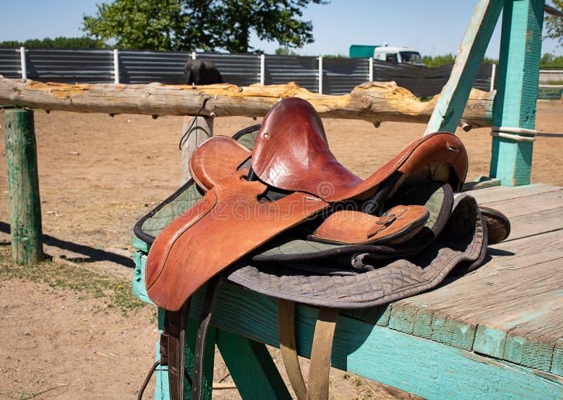 Pferdesattel auf hölzernem Brett, Bauernhofhintergrund stockfoto
