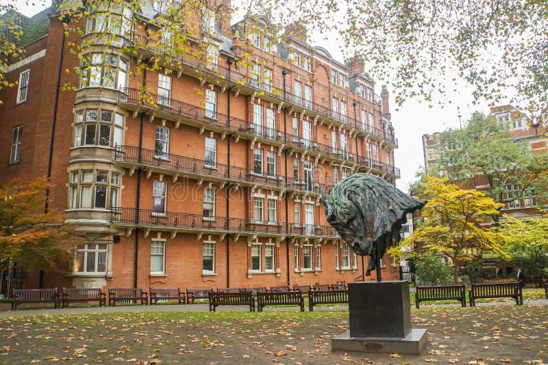 Pferdeskulptur in London-Park im Herbst mit Weinlesegebäudehintergrund stockfotos