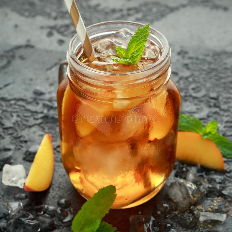Pfirsich-Eistee mit Minze im Glasgefäß, auf rustikalem schwarzem Hintergrund Sommerfrucht-Kältegetränke lizenzfreie stockbilder