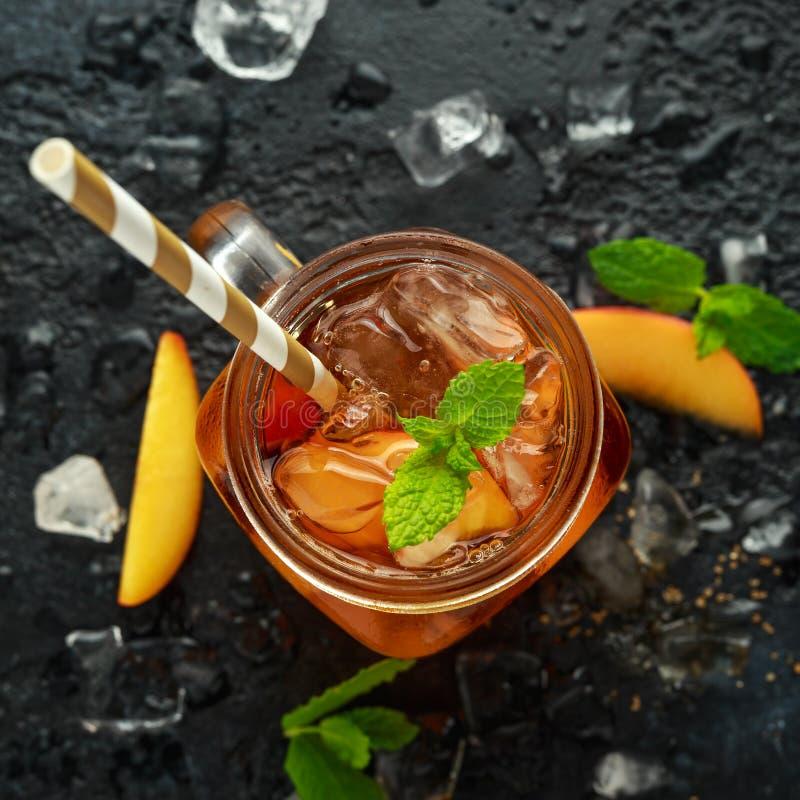 Pfirsich-Eistee mit Minze im Glasgefäß, auf rustikalem schwarzem Hintergrund Sommerfrucht-Kältegetränke stockfotos