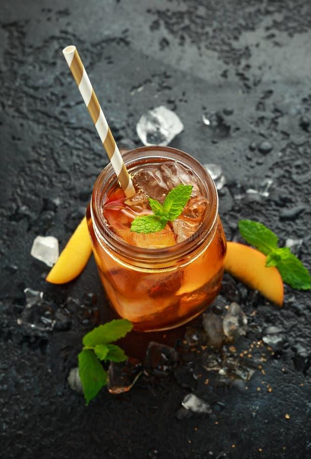 Pfirsich-Eistee mit Minze im Glasgefäß, auf rustikalem schwarzem Hintergrund Sommerfrucht-Kältegetränke lizenzfreie stockfotografie