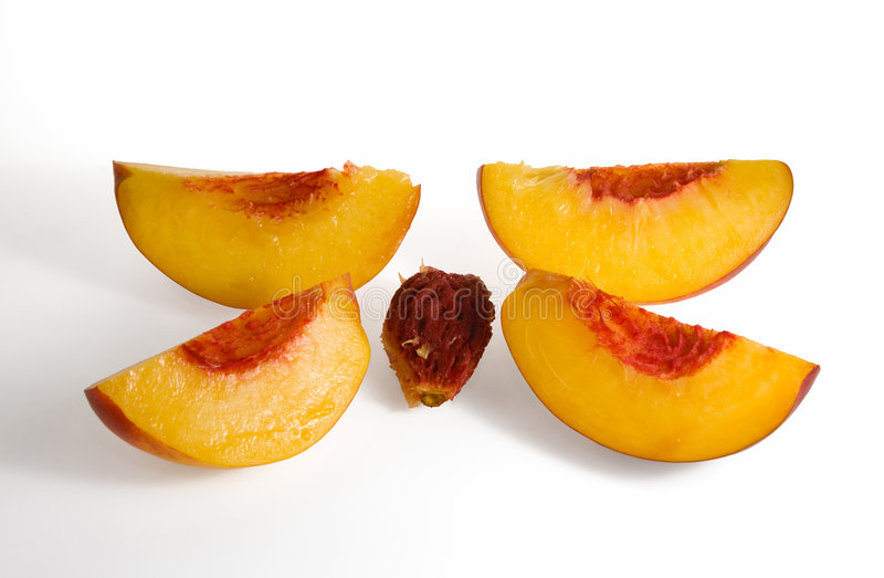 Pfirsich geschnitten auf vier und Frucht mit am Fleisch haftendem Stein lizenzfreie stockbilder