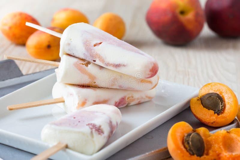 Pfirsichaprikose und orange Eis am Stiel auf weißer Platte mit neuem Franc stockbild