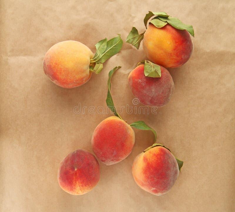 Pfirsiche auf braunem Papier stockfotos