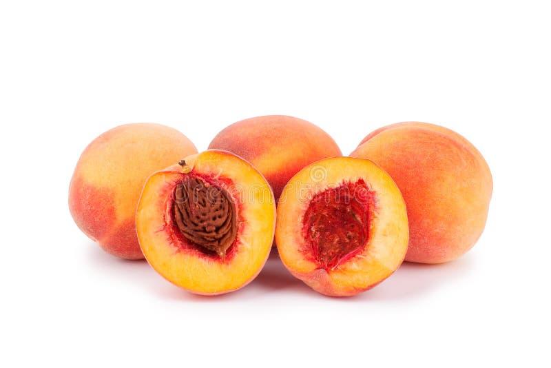 Pfirsiche ganz und zur Hälfte auf einem weißen Hintergrund cutted nah oben lokalisiert lizenzfreie stockfotos